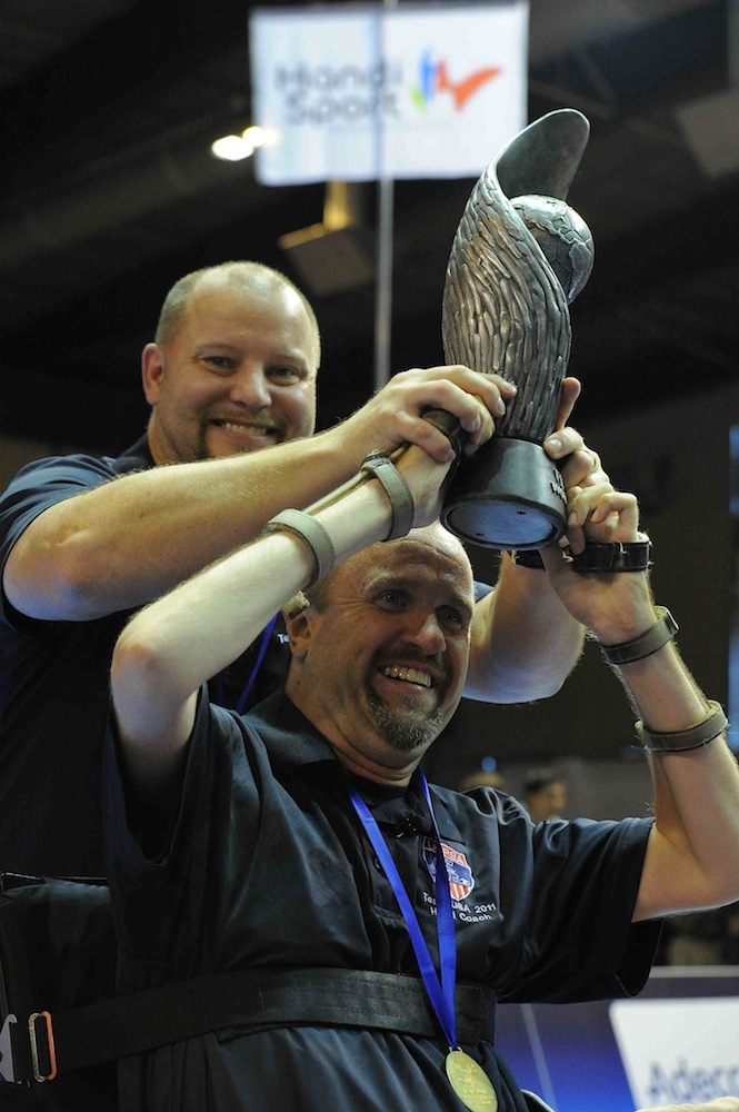 Head Coach Chris Finn (with help from Asst. Coach Mike Hayes) holds up World Cup trophy in victory.